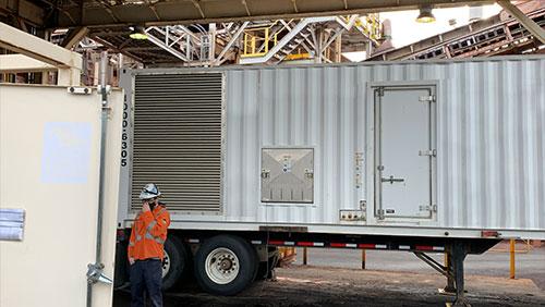 Technician standing by a generator